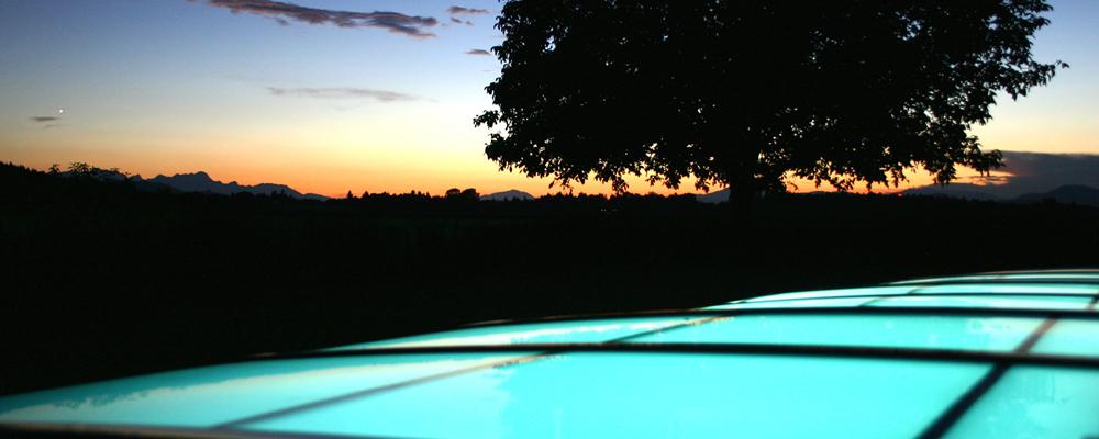 Sonnenuntergang hinter dem beleuchteten Pooldach