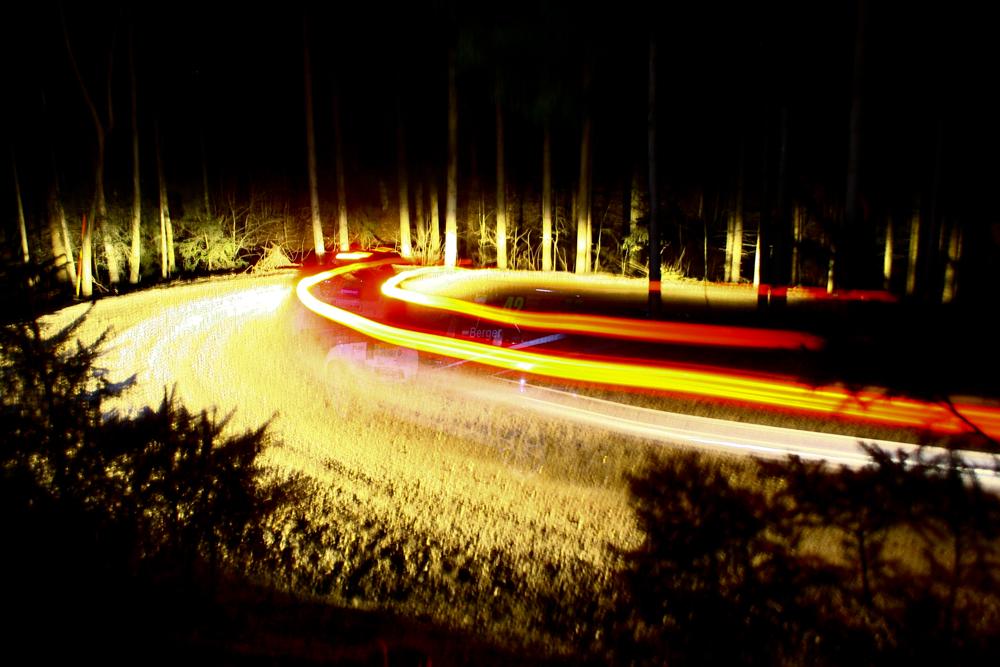 Nachtaufnahme eines vorbeifahrenden Rallyeautos