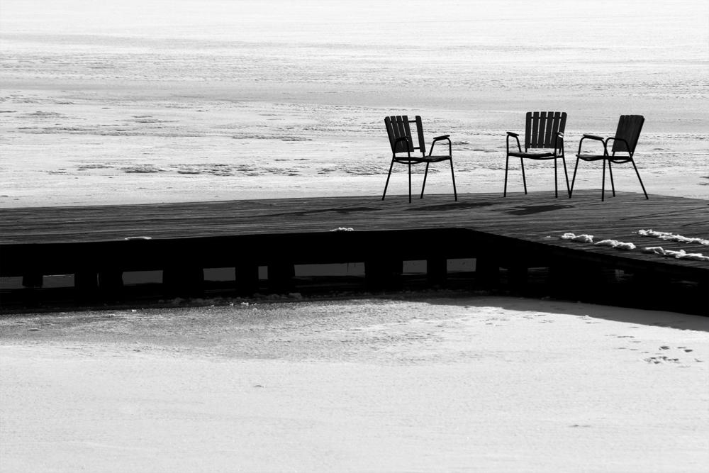 Verlassene Stühle am winterlichen Badesteg