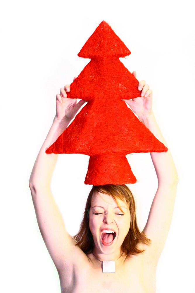 Junge Frau trägt roten Christbaum am Kopf
